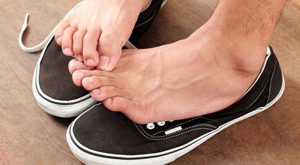 Fekete tornacipő felett egy férfi lába, ahol lábujjával a viszkető érzését vakarással orvosolja, valószínűleg lábgombája van.