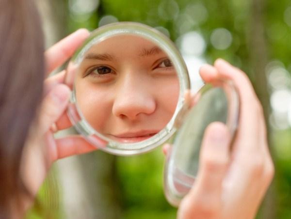 Fiatal lány kézitükörben nézi arcát kinn a természetben. A képen a tükörben látott kép éles, a többi részlet homályos.