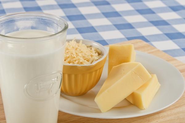 Kék-fehér kockás abroszon egy pohár tek, mellette kistányéron darabolt és reszelt sajtok.