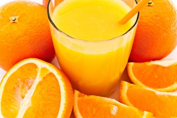 Félbevágott és egész narancsok, narancsszeletkék a képen, középen a gyümölcsből készült frissen préselt narancslé üvegpohárban, benne narancssárga szívószál.