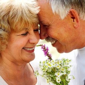 Idősebb pár mosolyogva összebújik. A férfi virágot ad a nőnek.