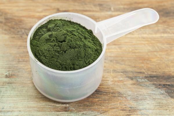 Spirulina alga por kis műanyag mérőedénykében egy kopott asztallapon.