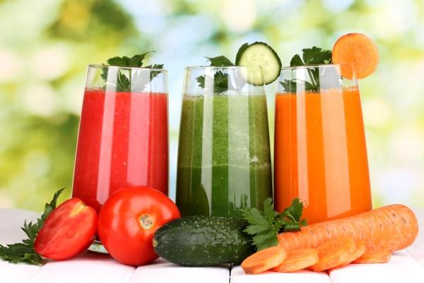 Frissen csavart zöldséglevek üvegpohárban: paradicsom-, uborka- és sárgarépalé.