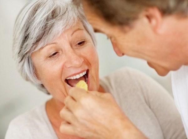 Idősebb férfi házastársa szájába tesz egy gyümölcsfalatkát.