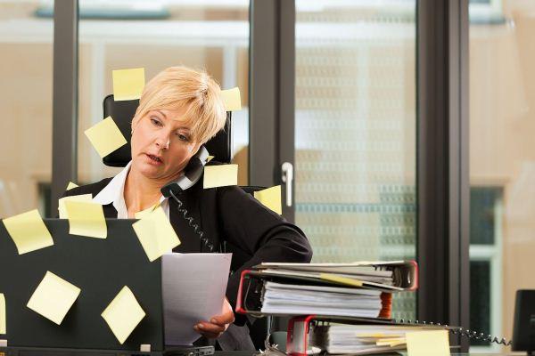 Idősebb hölgy irodai asztalán rengeteg dosszié, telefonál, közben nézi a monitort. A számítógépe és a széke is tele van felragasztott papírokkal.