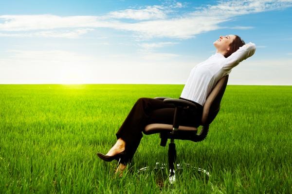 Irodai széken ül hátradőlve egy üzletasszony, mindezt egy zöld rét kellős közepén.