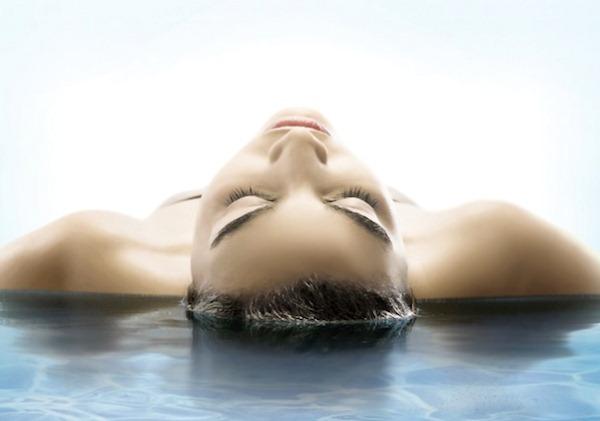 Kék tengervízbe fekvő hölgy a homloka felől fotózva.