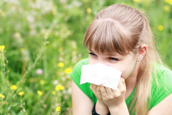 Virágos, zöld mezőben egy fiatal lány papírzsebkendőbe tüsszög.