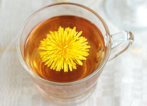 Pitypangtea üvegpohárban felülről fotózva, a tea közepén a növény sárga virága.