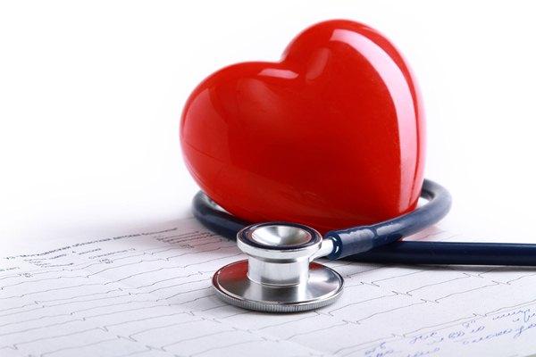 Piros műanyag szív, körülötte fonendoszkóp, alatta EKG-s görbe.