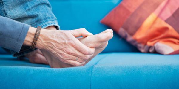 Idős férfi kék kanapén lábfejét fogja.