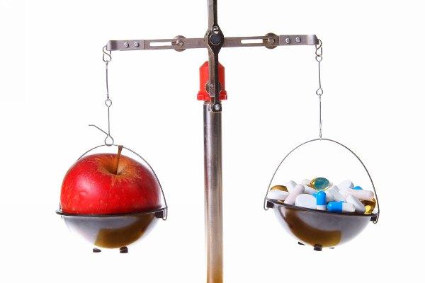 Mérleg egyik serpenyőjében egy szép, piros alma, a másikban mindenféle gyógyszerek vagy étrend-kiegészítő kapszulák.