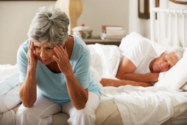 Fejét fogó hölgy ül az ágyban pizsamában, férje békésen alszik.