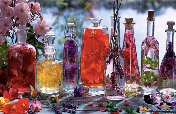 Különböző színű rózsákból rózsaecet többféle átlátszó üvegben.