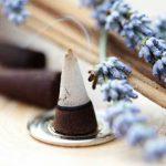 Levendulával illatosított kúp alakú füstölő, mellette lila levendula virágja.