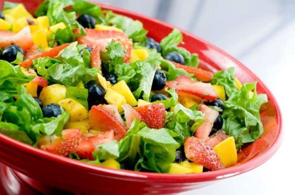 Piros tányéron friss saláta zöldségekkel, olivával, eperdarabokkal.