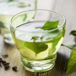 Üvegpohárban zöld tea, benne egy friss tealevéllel, mellette szárított tea.