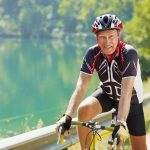 Idős férfi versenykerékpárján ül biciklis ruhában, védősisakkal a fején.
