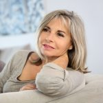 Hosszú hajú, idősebb nő ül a kanapén, keze a tarkójánál.
