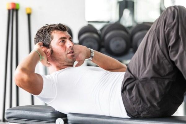 Hasprést végez egy középkorú férfi az edzőteremben.