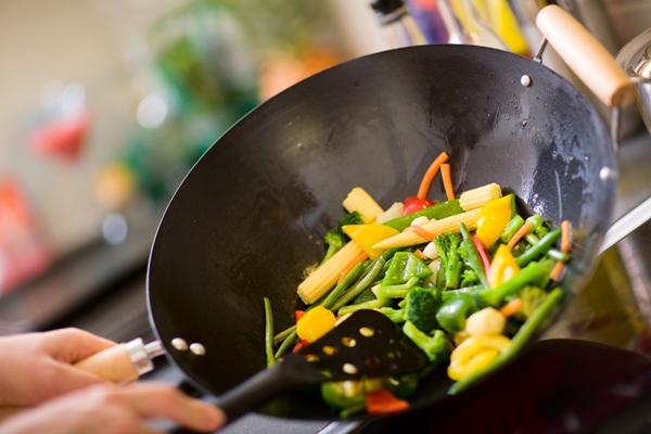 Wokban pirítanak apróra vágott zöldségeket.