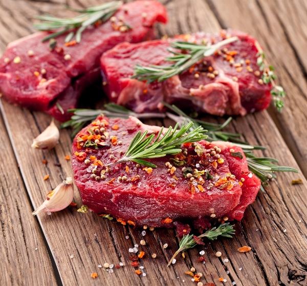 Szeletelt húsok meghintve fűszerekkel egy rusztikus faasztalon, mellettük fokhagyma, a húsokon rozmaringágacskák.