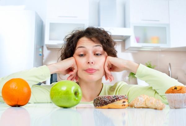 Középkorú nő a konyhában vívódik a pultra kirakott gyümölcsök és az édességek között.