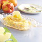 Üvegből készült almareszelő, rajta almával, a háttérben kistányér, villa, kanál és piros almák.