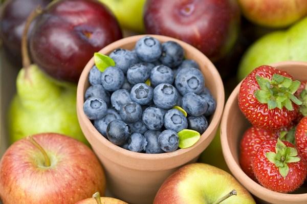 Színes almák között két cserépben frissen szedett áfonya és eper.