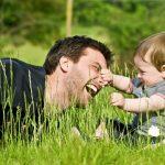 Fiatal férfi játszik kisfiával a réten a fű között, a baba épp apukája orrát markolássza, aki nevet közben.