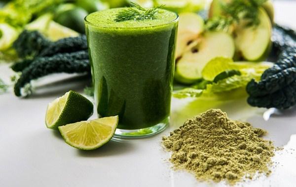 Zöld turmix és alkotóanyagai: fűlevek, algapor, lime, zöldalma, zöld fűszerek.