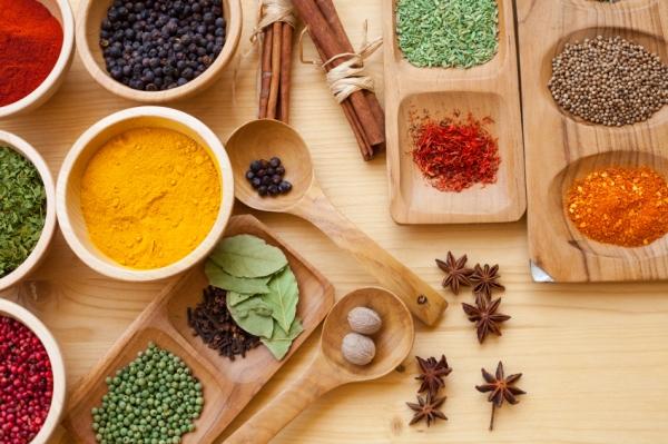 Ájurvédikus ételek, fűszerek csoportonként lerakva fatálkákba, fakanalakba.