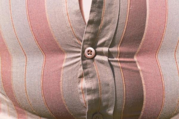 Kövér ember hasán feszülő csíkos ing.