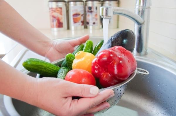 Szűrőben tisztára mosott zöldségek és gyümölcsök a mosogatóban.