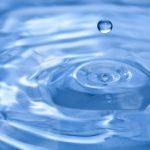 Kéken fodrozódó vízbe hullik egy csepp víz.