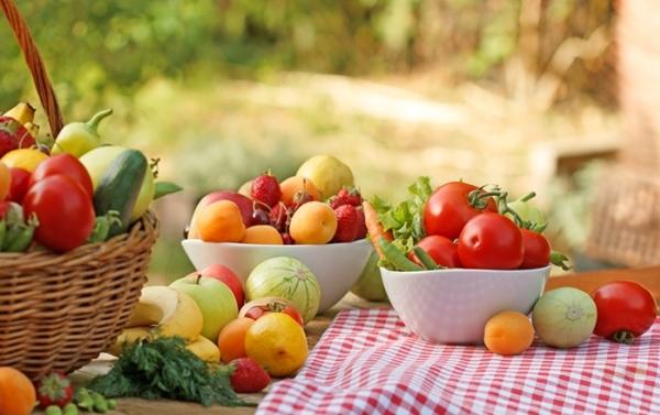 Piros kockás abrosszal leterített kerti asztalon kosárban, tálakban friss zöldségek és gyümölcsök.