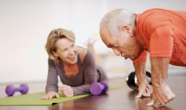 Egyujjas fekvőtámaszt nyom egy idősebb férfi, mellette zöld jógamatracon egy hölgy számol neki mosolyogva.