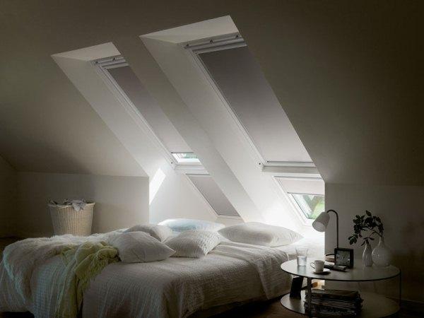 Félig lehúzott rolók mellett nappali félhomály egy tetőtéri hálószobában.