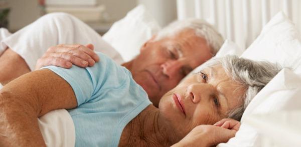 Idősebb házaspár ébren fekszik az égyban, a férfi réteszi felesége vállára a kezét.