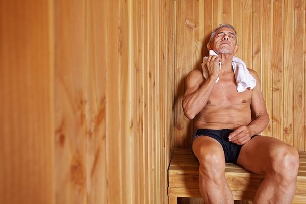 Idősebb férfi a szaunában ülve törli a nyakát egy törülközővel.