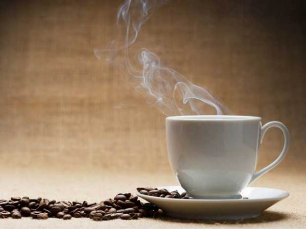 Fehér csészében gőzölgő kávé, mellette kávészemek.