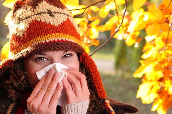 Mosolygós szemű nő fújja papírzsebkendőbe az orrát kötött sapkában, háttérben színes, őszi falevelek.