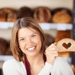 Pékségben egy mosolygós eladó egy teljes kiőrlésű kenyér szeletkéjét tartja a kezében, melyből kivágtak egy szív alakot.