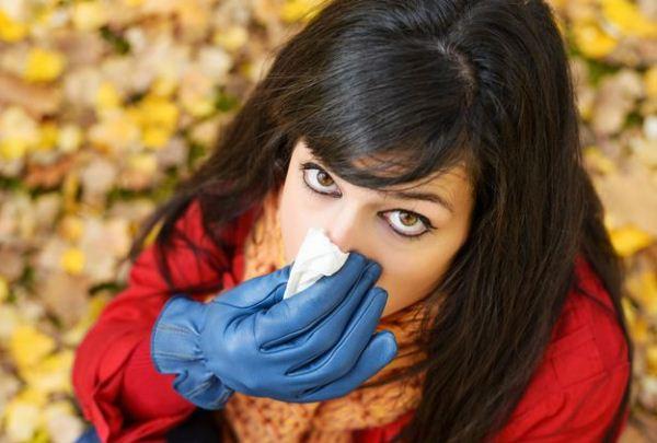 Fiatal nő sálban, kék bőrkesztyűben ránk néz, kezében zsebkendő, lába alatt színes falevelek.