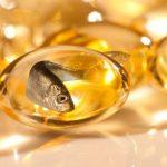 Omega-3 zsírsavat tartalmazó sárga gélkapszulák, melyekben halak úszkálnak, utalva ezzel a halolajra.