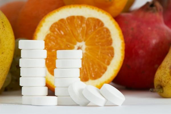 C-vitaminok egymásra halmozva, mögöttük félbevágott narancs és különféle gyümölcsök: körte, gránátalma.
