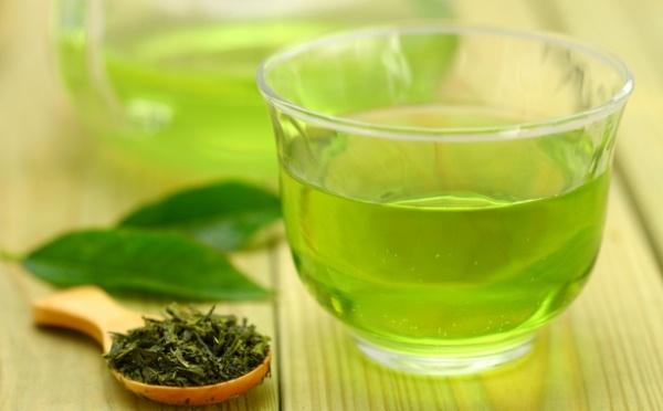 Üveg pohárban zöld tea, mellette szárított és friss tealevelek.