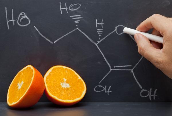 A C-vitamin kémiai képletének felírása fehér krétával egy fekete táblára, az asztalon egy félbevágott narancs mint C-vitamin-forrás.