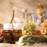 Szárított gyógynövények tálkákban, illóolajok üvegcsékben, kicsi Buddha szobor egymás mellett, az ájurvéda gyógyító eszközei.