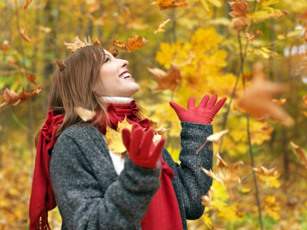 Piros kesztyűben és ugyanilyen színű sálban, meleg pulóverben egy fiatal lány mosolyogva nézi a lehulló faleveleket az őszi erdőben.